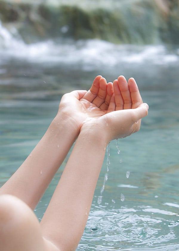 女性が温泉を救い上げる様子